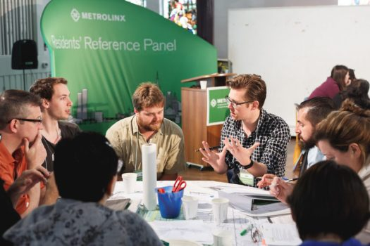 Photo of citizens meeting at a table to learn and discuss Metrolinx reform. Democratic innovation at work!
