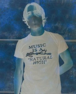"""A photo negative of a person in a mask a shirt reading """"Music Is a 'Natural High'""""."""