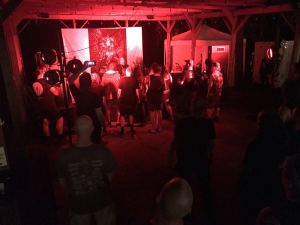 Traitor plays in a picnic shelter with bright red lights.