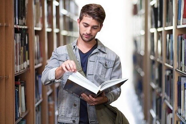 Opiskelija kirjastossa lukemassa kirjaa