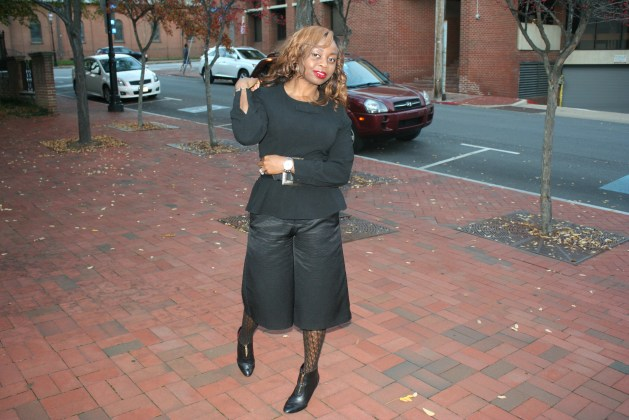 Black culottes with black peplum top, black patterned tights and black boots