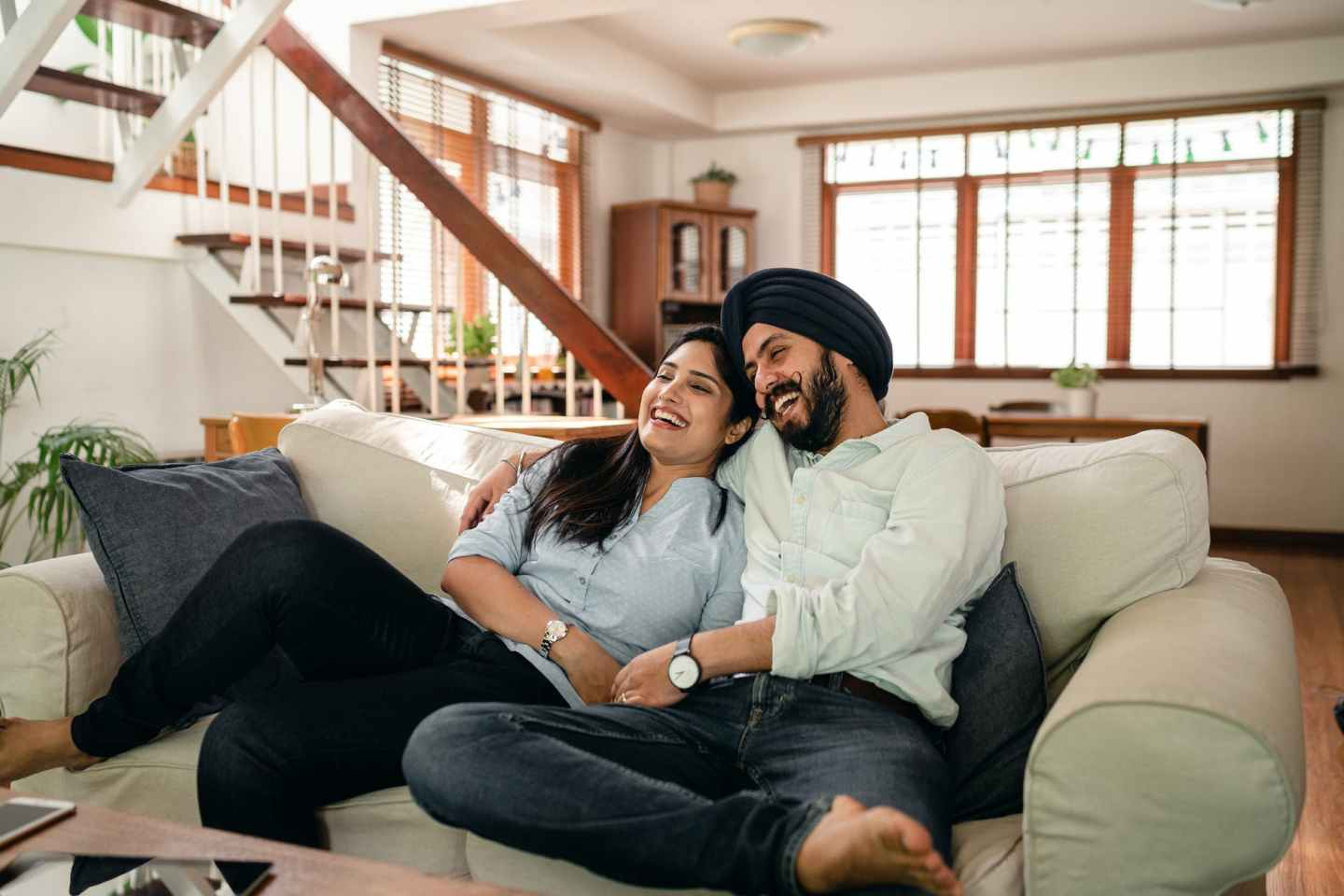 happy Indian couple laughing and watching a movie at home