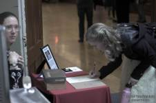 My mother at the welcome desk; a guest signing in