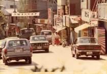 (昭和54年)観光ブームの頃の通りの様子。「祝与論港初接岸」(供利港)の横断幕が見えます。 それにしても、路上の車は、勝手な方向に走っているように見えませんか?