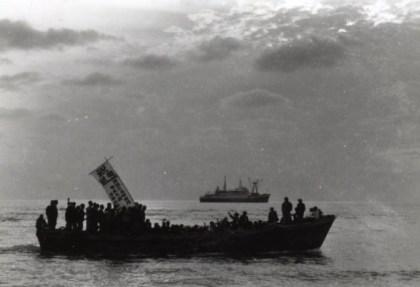 本土への集団就職生を満載して沖の本船へ向かうハシケ。幟(のぼり)は「祝就職 ・・・・」と読めます。
