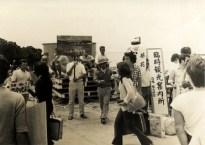 昭和49年頃の光景。まさしく臨時案内所で屋根もありません。 看板を持った各民宿の従業員が船から下りてくる観光客達を迎えていました。