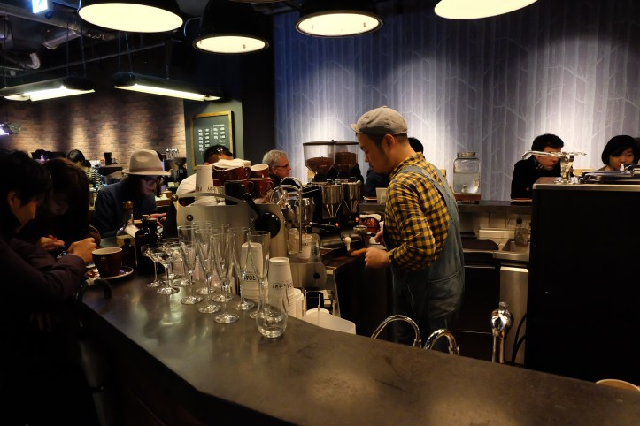 Barista working on Synesso Espresso Machine while customers sit at the bar at The Roastery by Nozy Coffee in Shibuya Tokyo Japan