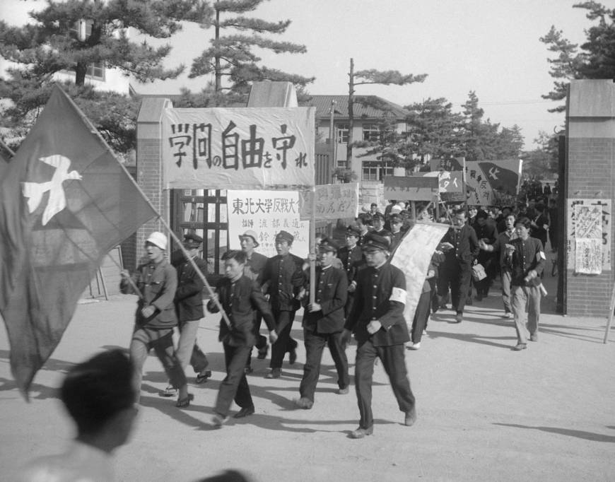 Venerable site: Students taking part in an anti-war rally file out through the gates of Tohoku University in Sendai in 1950. The storied university recently revealed that it plans not to renew the fixed-term contracts of up to 3,200 employees, thereby ensuring that they will not be able to become regular staff according to a recent revision to the Labor Contract Law. | KYODO