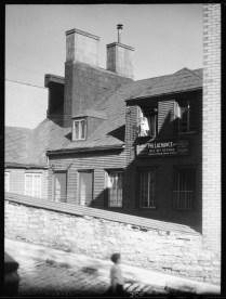 Rue St-Paul, 1932. Clifford M. Johnston / Bibliothèque et Archives Canada / PA-056553 A droite, on aperçoit une petite fille au balcon et l'enseigne de Philéas Lachance, plombier, 163-167 St-Paul.