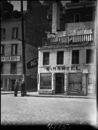 """The Corner Pub"" - Clothes hangin out to dry. 1933, C.M. Johnston / Bibliothèque et Archives Canada / PA- Epicerie de Severin Martel coin Laplace 2-6 et Thibaudeau. Taverne G. H. Roy"