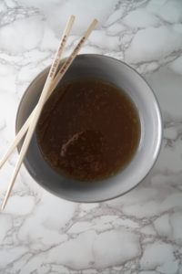 A bowl with broth and chopsticks for a Asian Chicken noodle soup bowl