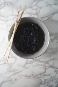 A grey bowl with chop sticks, broth, and black noodles for Asian Chicken noodle soup bowl