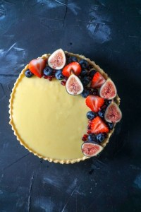 A fruit tart topped with fruits on the right side