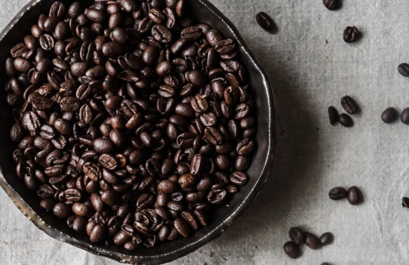 A bowl of coffee beans with some spilled out