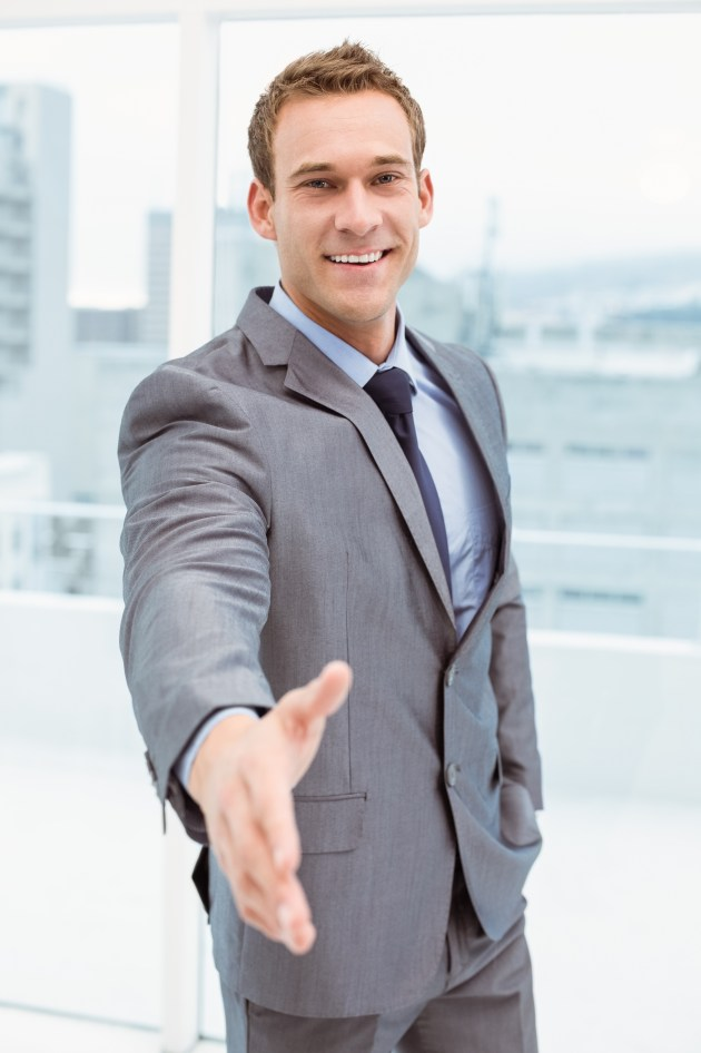 Portrait of smart businessman offering handshake