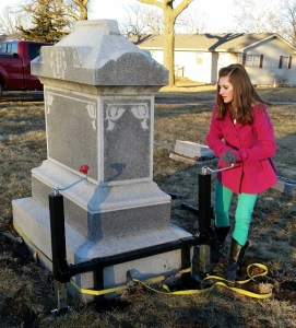 Young woman lifting heavy monument by herself using the Tombstone Jack