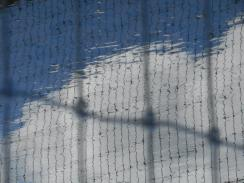 Looking through one fence at another fence reflected in a puddle with the sky and clouds 4-4-15