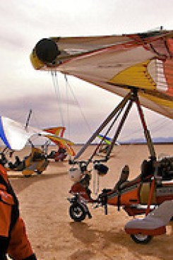 John McAfee stands in the New Mexican playa in front of his trike ultralight, during a Sky Gypsies aerotrekking camping expedition. (Tom Clynes)