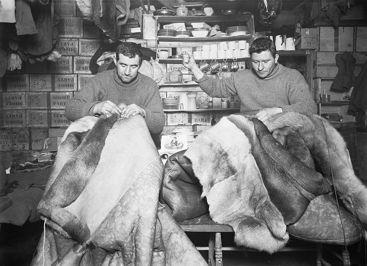 Tom Crean and Edgar Evans mending sleeping bags in 1911.