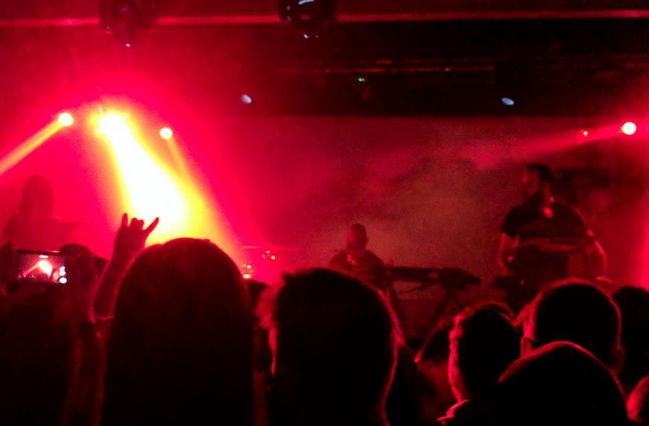 Carpenter Brut playing live under crimson lighting.