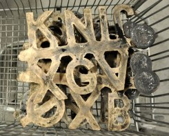 Bronze letters pulled from the sand molds, wait to be finished.