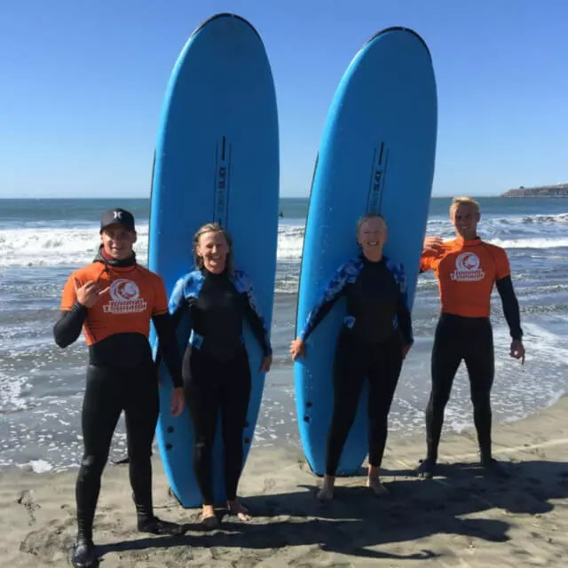 Tommy Tsunami Surf School instructors with two students