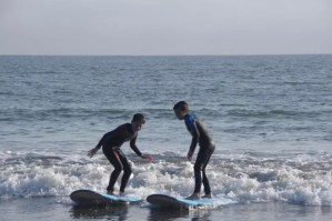 two kids standing up on the surfboards
