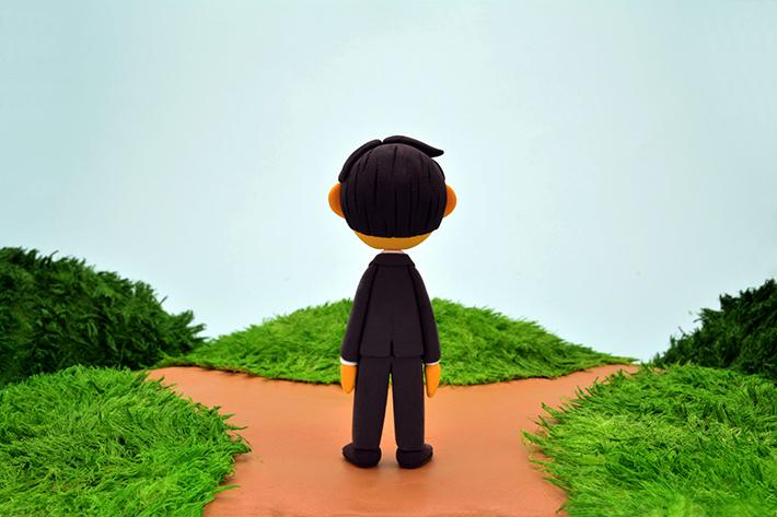 分かれ道に立つ男性のイラストイメージ