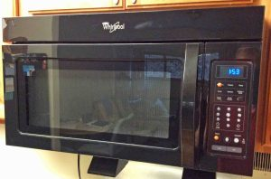 Picture of the Whirlpool Over The Range Microwave Oven, Model WMH31017AB, fully installed and operational.
