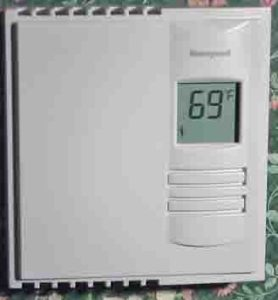 Picture of Honeywell thermostat models, the 5-2 baseboard heating Thermostat RLV310A, shown mounted on wall and operating.