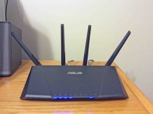 Picture of the Asus RT-AC87R WiFi router, front view, installed and operating on office desk. How to choose a wireless router.