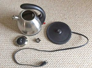 How to clean stainless steel tea kettle. Picture of the Hamilton Beach 40891 stainless steel tea kettle, Disassembled, showing the kettle, strainer, lid, and power stand.