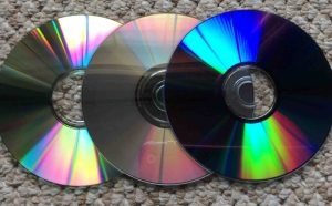 Picture of typical data CD, music CD, and DVD discs. How to clean CDs and DVDs.