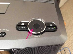 Picture of the Volume knob on the top of the radio, highlighted by the pink arrow.