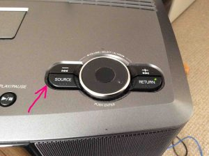 Picture of the Denon S-32 Music Center, showing the Source button location, highlighted by the pink arrow.