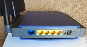 Picture of the back view of the Linksys WRT300N Wi-Fi Router, showing the antennas (left), wide area and local Ethernet ports, reset button, and power port.