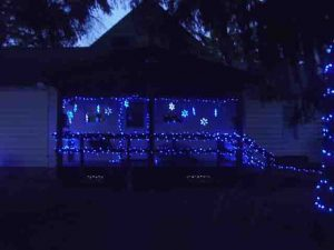 Picture of Blue LED Christmas Light Decorations Outdoors, house south porch, showing LED snowflakes, and small LED strings on porch railings and banisters.
