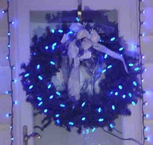 Picture of Blue LED Holiday Lights, decorated wreath hanging on west door at our home.