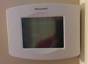 Picture of the Honeywell RTH8580WF Thermostat, displaying blank screen during factory reset operation.