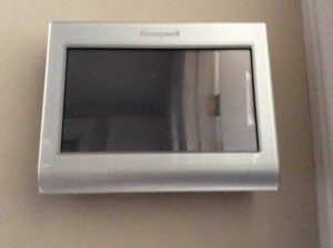 Picture of the RTH9580WF internet t-stat, mounted but powered down, snapped onto wall plate.