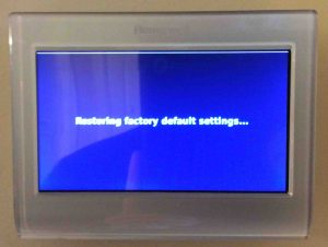 Picture of the Honeywell RTH9580WF smarttThermostat, showing the Restoring Factory Default Settings screen during reset. Honeywell RTH9580WF thermostat reset.