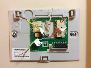 Picture of a Honeywell thermostat wall plate, mounted, but with wires not yet connected.