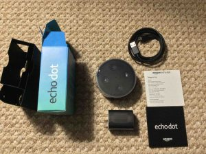 Picture of the Amazon Echo Dot 2nd Gen speaker, original package, with Items inside unpacked.