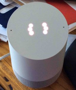 Picture of the original Google Home speaker, with a reset in progress, displaying a white spinning light ring pattern.