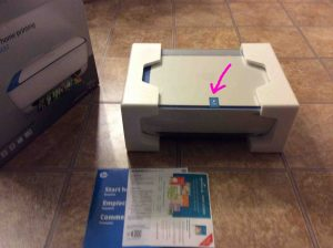 Picture of the HP printer 3632 with user guides and software disc out of box, with blue tape highlighted.