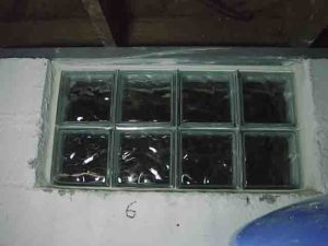 How to install glass block windows. Picture of the Basement Glass Block Window Replacement 6, with white mortar applied and shims removed.