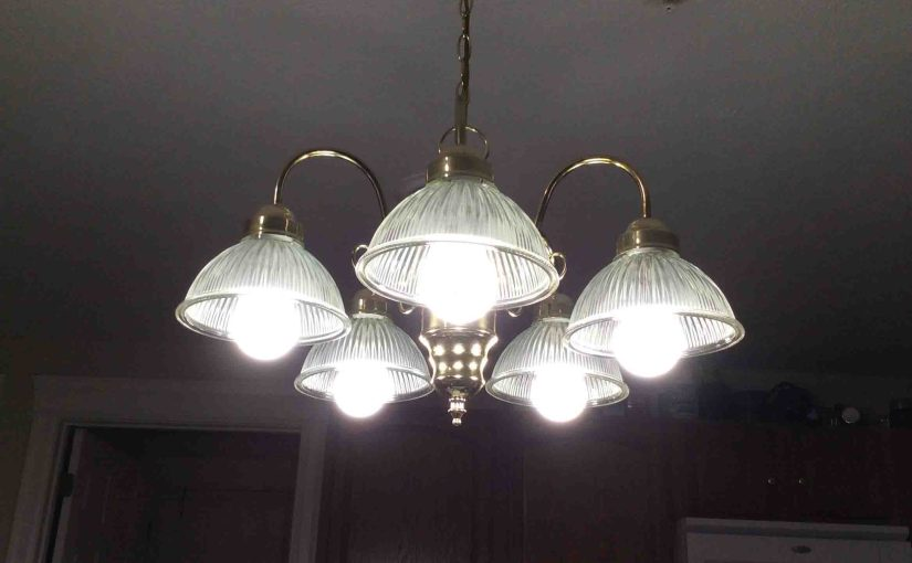 Picture of five Ecosmart™ LED 60w A19 daylight white light bulbs, operating in dining room chandelier.