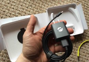 Picture of the power adapter for the Google Chromecast Audio receiver, held in hand.