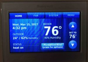 Picture of the Honeywell RTH9580WF thermostat, displaying its -Home- screen, after new temperature range limits were applied.