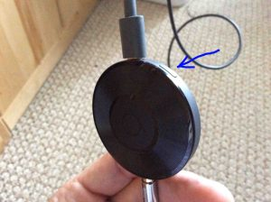 Picture of the Google Chromecast Audio receiver, front view, reset button highlighted.